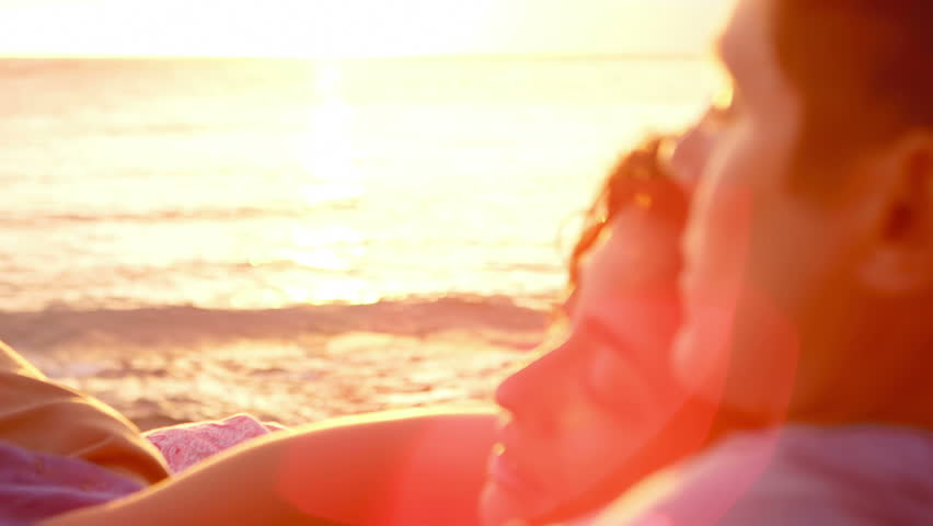 A woman lays on a man's chest as they sit on the beach and watch the sun set together #4776395