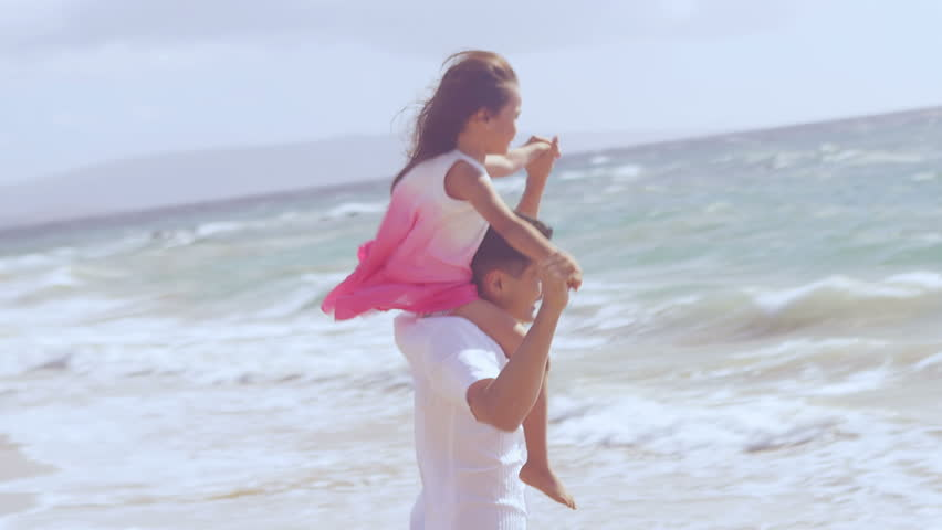 A father holds his daughter on his shoulders and runs around at the edge of the water at the beach
