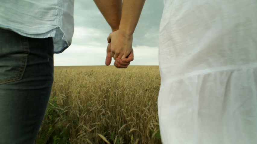 Couple walking then running across the cultivated land holding hands