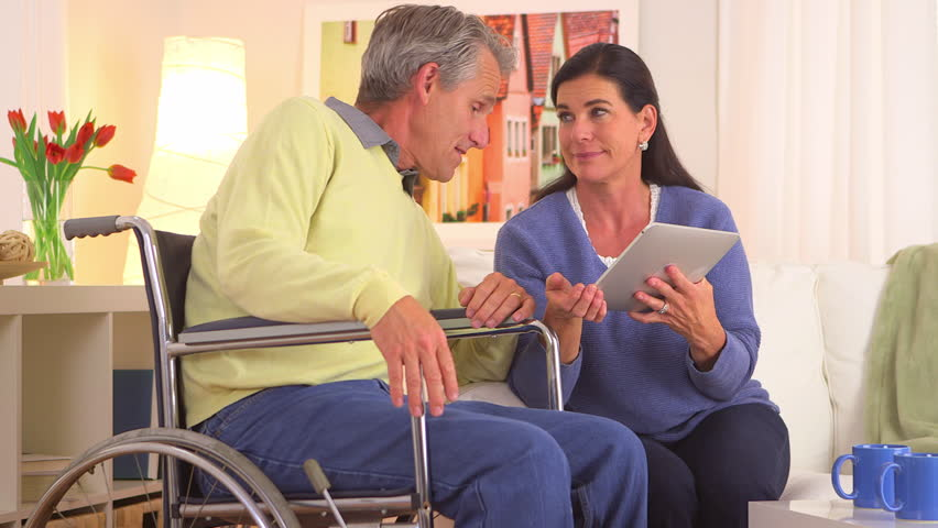 Senior couple happily talking with tablet