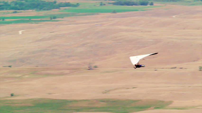 DAYTON, WYOMING – August 17, 2012: A hang glider soars over a valley in Dayton, Wyoming.
