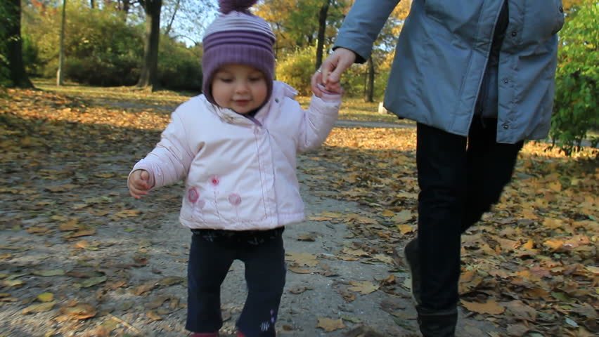 Baby hold her moms hand and learns to walk in a park