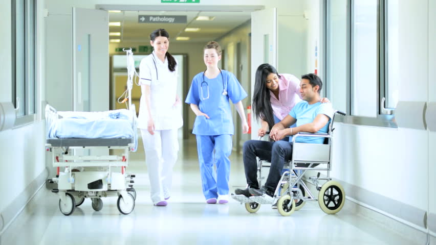 Female nursing staff walking through hospital corridor passing young South Asian family spending quality time together | Shutterstock HD Video #4807490