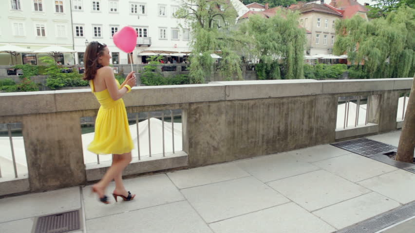 Cute woman walking with a balloon in hand. High definition video shot on Steadicam.