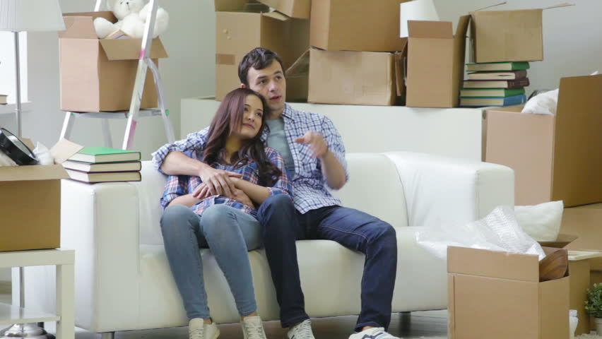 Couple carrying stuff while moving in then cuddling on the sofa to take a break | Shutterstock HD Video #4827335