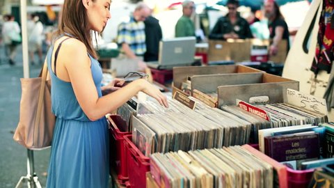 Young woman looking at old vinyl records at flea market