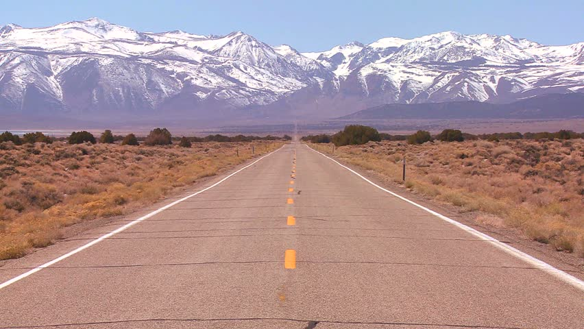 A long straight lonely road heads to the mountains.