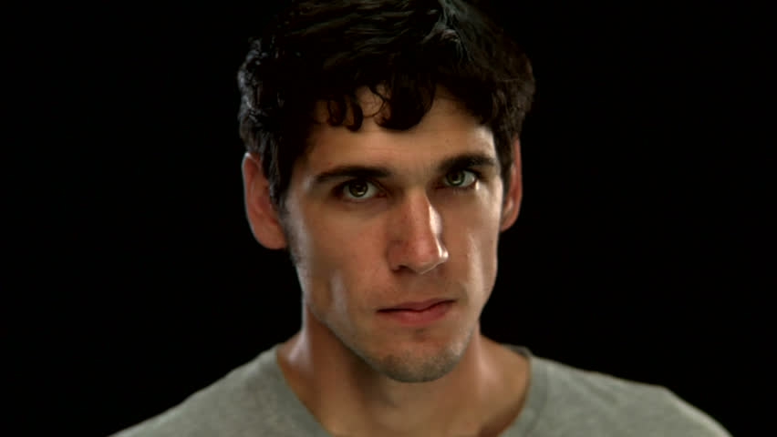 A young man makes an angry face on a black background