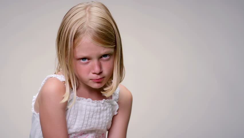Young blonde girl makes an angry face against a white background