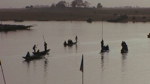 Boats are rowed in silhouette on the Niger River in mali, Africa.