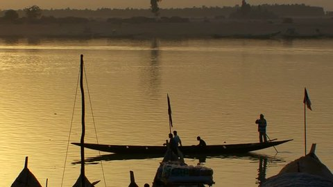 Boats are rowed on the Niger River in beautiful golden light in Mali, Africa.