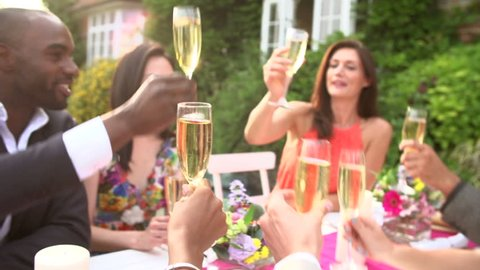 Slow motion close up view of friends proposing champagne toast at outdoor dinner party