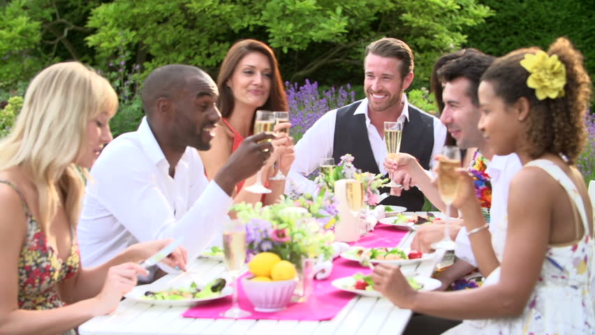 Slow motion sequence of young adults enjoying fancy outdoor dinner party with champagne