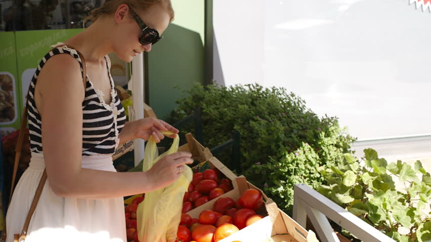 Young woman shopping for fresh vegetables at an open-air market choosing ripe red tomatoes