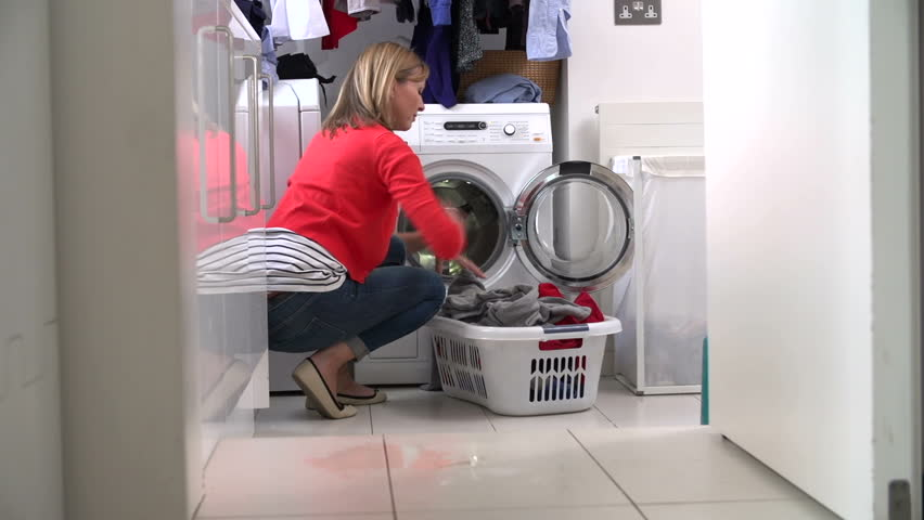 Middle aged woman fills washing machine with clothing from laundry basket