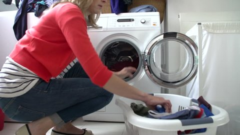 Housewife fills washing machine from laundry basket and locks machine door
