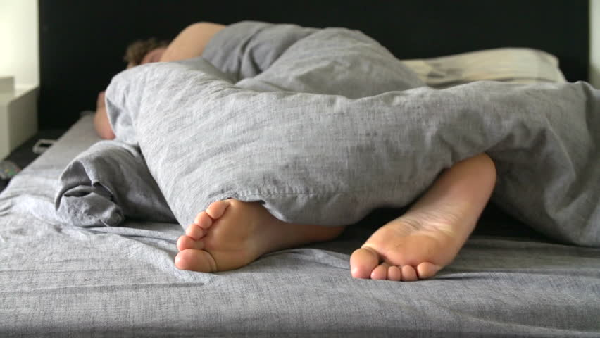 Teenage Boys Feet Poking Out Of The Bottom Of The Duvet As He Sleeps In Late