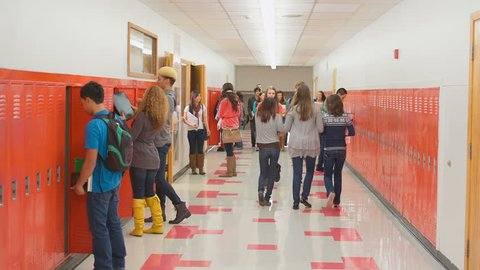 An empty school hallway fills up with students when the doors open at the end of the period