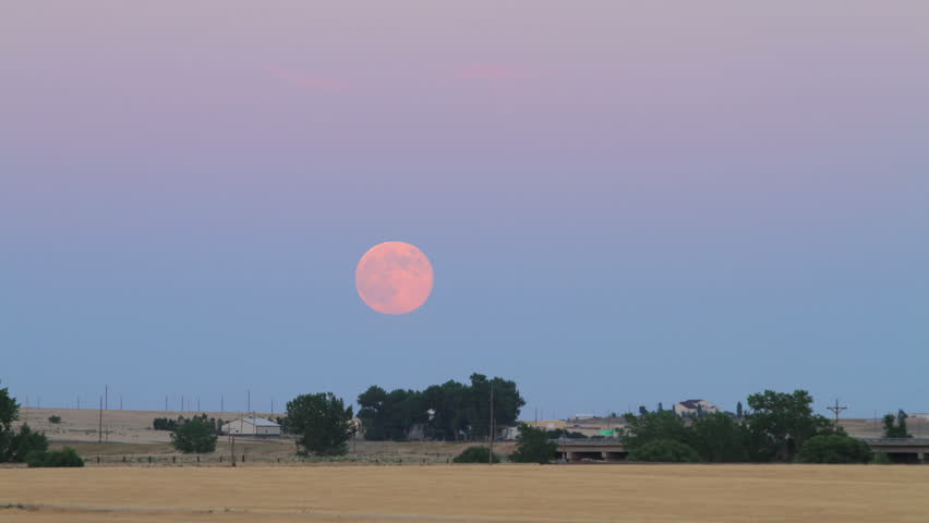 The July Supermoon Full Moon rises over Interstate 25 Highway at dusk in rural eastern Colorado. HD 1080p.
