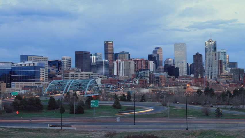 Denver skyline at dusk, with fast moving traffic on the interstate. Ultra HD 4k