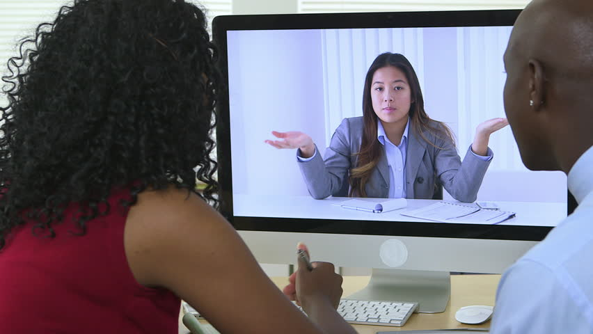 Black business partners holding teleconference with Asian colleague