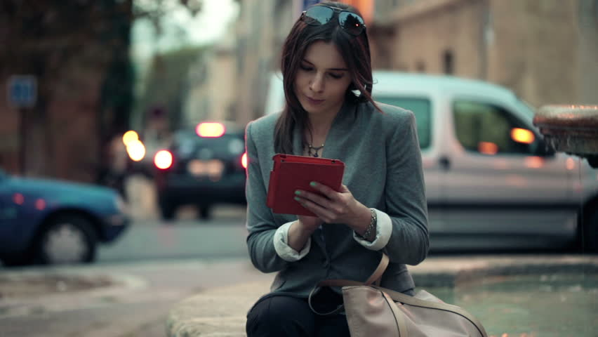 Elegant beautiful woman with tablet computer in the city
