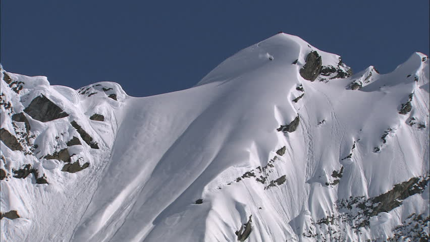 Skier carving down a steep and technical face in the Alaskan back country.