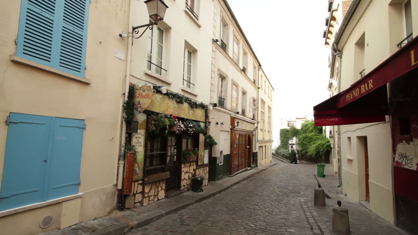 PARIS, FRANCE - CIRCA JULY 2013: Young man on a moped drives down a street at the famous Montmartre district in Paris.