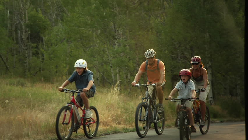 Family bicycle riding on forested trail, Park City, Utah.