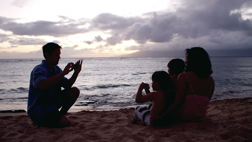 A silhouette of a man taking a picture of his family while they sit in the sand at the beach at sunset