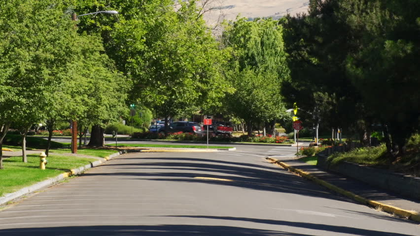 Cars on small town main street pass empty parking lot on college campus