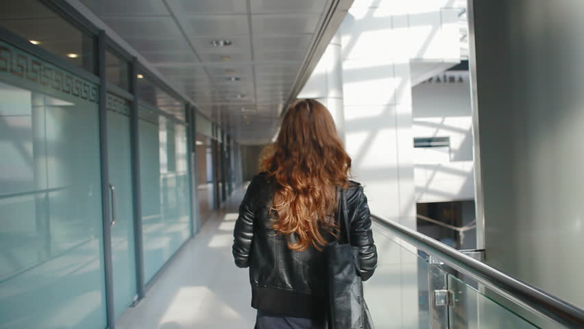 Beautiful girl goes on an office building, she turns around and looks very happy and fun | Shutterstock HD Video #4946519