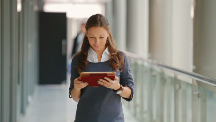 Young, attractive business woman with tablet computer in office building. girl dressed in comfortable clothes, against the background of elevator rides. she looks very happy and successful | Shutterstock HD Video #4946618