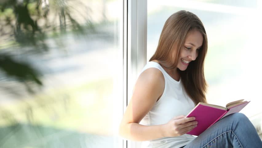 Beautiful girl sitting by window reading book closing it and smiling at camera