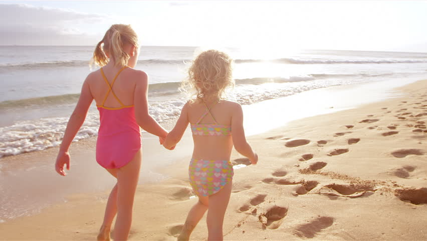 Two adorable little girls hold hands and walk down a beautiful beach together. Wide shot.