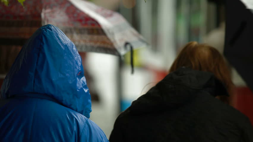 People waiting at the bus stop under rain