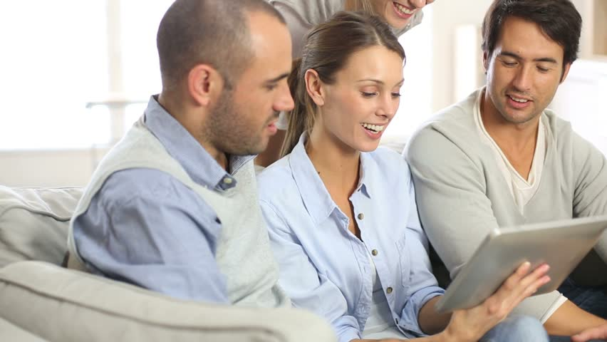 Friends gathering at home and using tablet