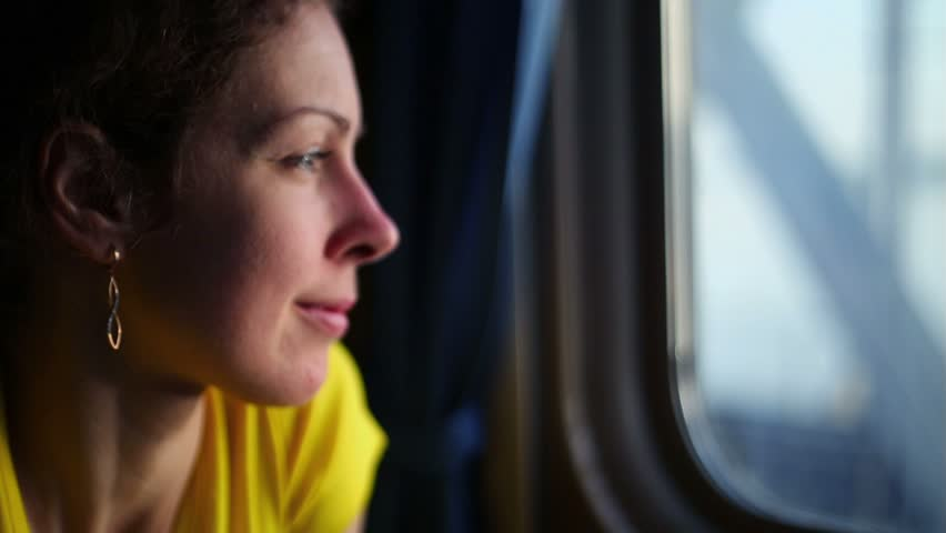 Flashes of sunlight on women face which watches in window of train during ride by bridge