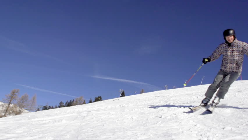 Slow Motion Of Skier Carving Down The Slope And Spraying Snow Onto The Camera