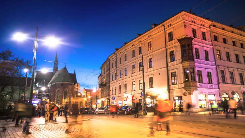 On the busy street in the center of Krakow at night time, near the main square,