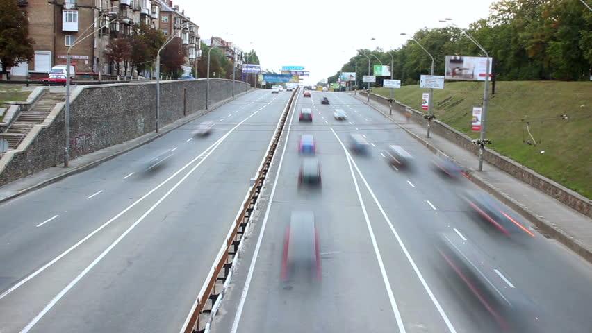 Small city street time lapse, cars drive both ways, bridge
