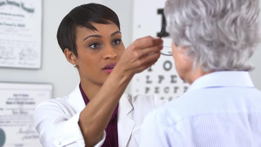 African American optometrist gives eyeglasses to senior woman #5066945