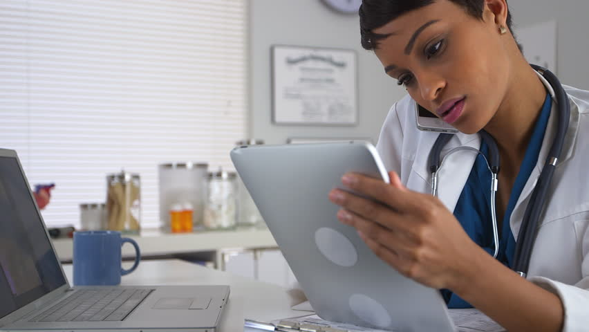 African American doctor talking on smartphone and looking at devices