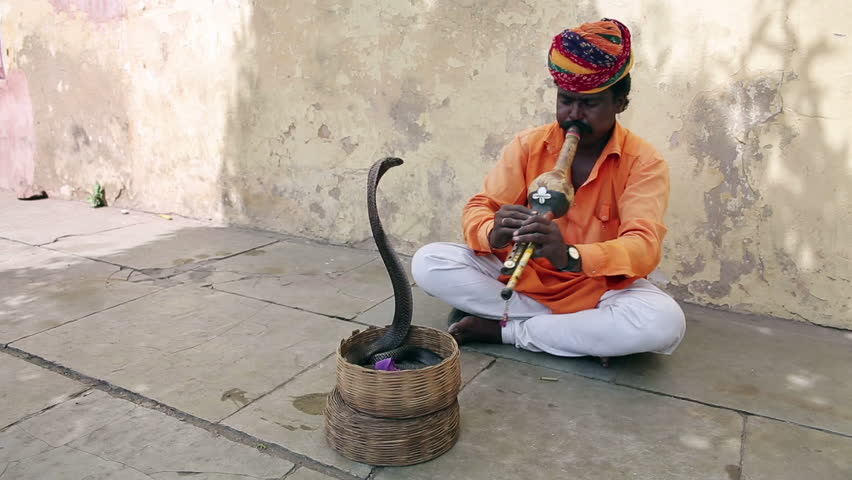 Cobra enchanter sitting in the street charming his snake
