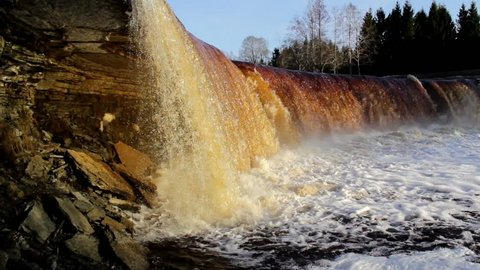 Estonian bigest and famous waterfall in spring. Cloud of water bubbles forming as the heavy currents of the water falls on the water below making a loud noise Estonia in Baltic states.