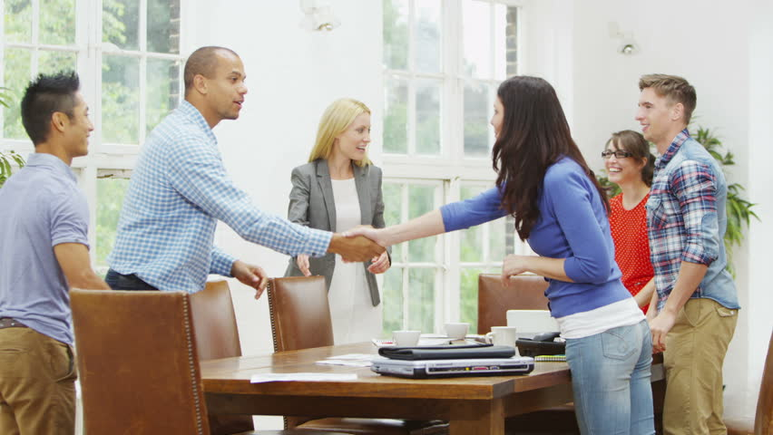Attractive casual business team shake hands and greet each other before taking their seats for a business meeting. In slow motion.