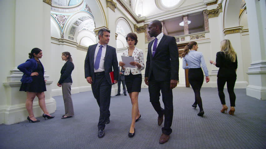 Diverse group of business or political delegates meeting for a conference in an elegant, classically designed building with a domed ceiling.