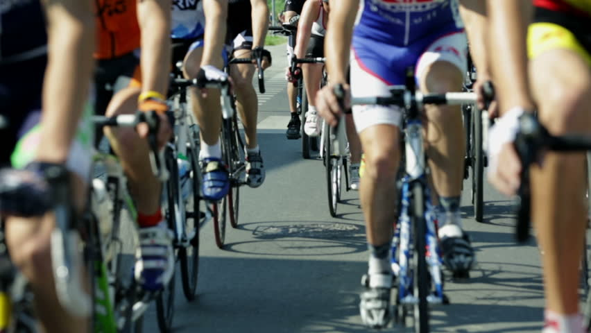 Shallow focus shot of cyclists lower bodies while riding bikes in cycling race