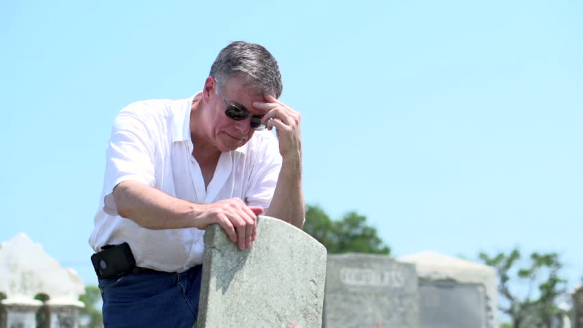 Upset mature man visiting grave
