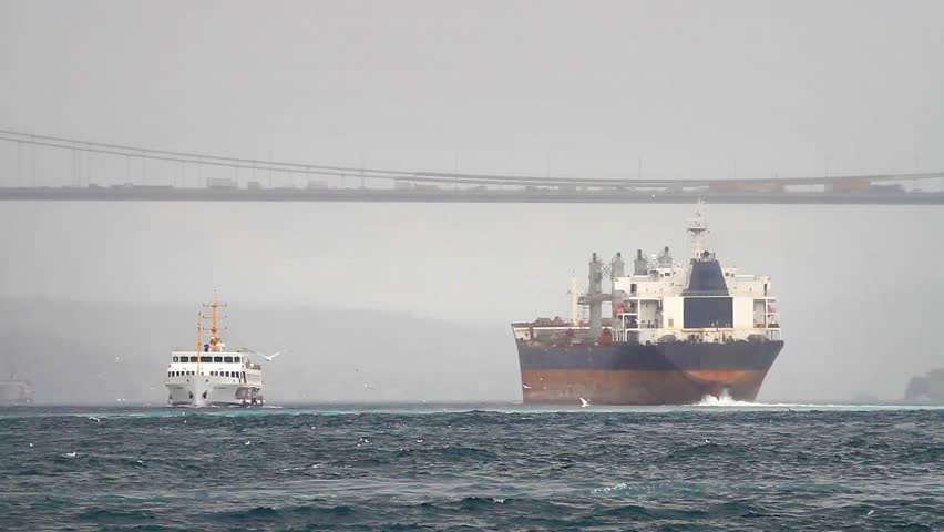 Sea Transportation. Cargo ship sailing out the harbor in winter.